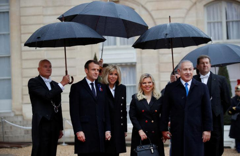 French President Emmanuel Macron and his wife Brigitte Macron welcome Israel Prime Minister Benjamin Netanyahu and his wife Sara at the Elysee Palace as part of the commemoration ceremony for Armistice Day, 100 years after the end of the First World War, in Paris, France, November 11, 2018 (photo credit: REUTERS/PHILIPPE WOJAZER)
