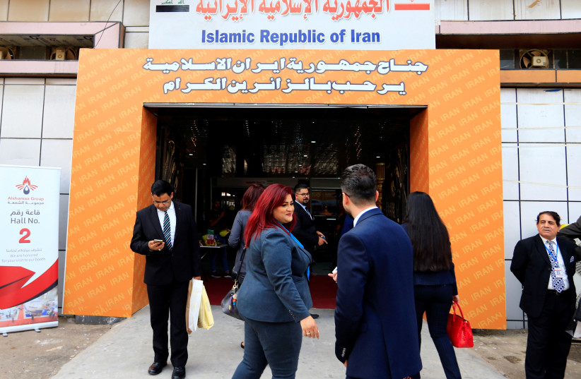 People walk in the entrance of the Iran section of the Baghdad International Fair, in Baghdad, November 10, 2018 (photo credit: THAIER AL-SUDANI/REUTERS)