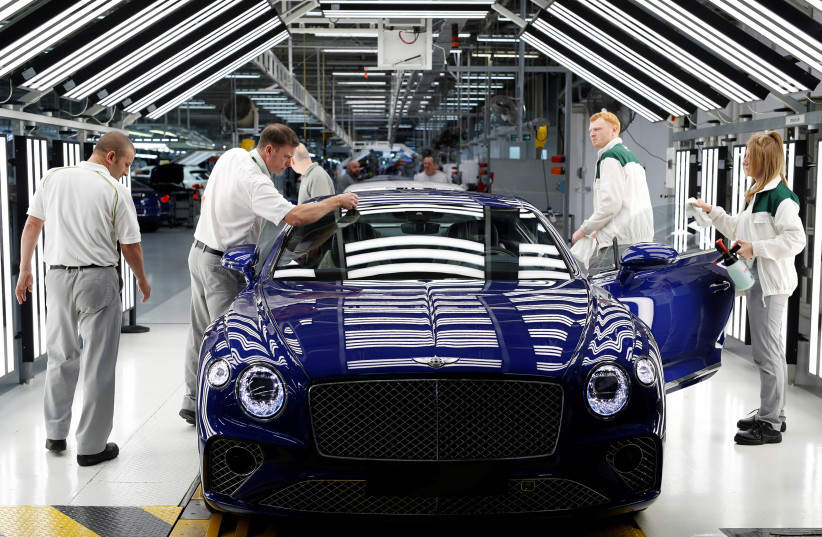 Workers inspect a Bentley Continental GT at the luxury automaker's manufacturing facility in Crewe, Britain October 15, 2018. Picture taken October 15, 2018.  (photo credit: DARREN STAPLES/REUTERS)