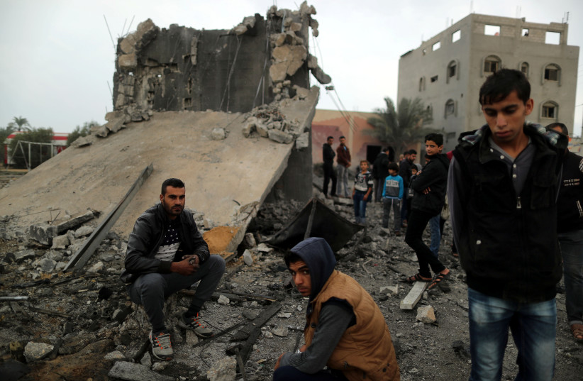 Palestinians sit at the remains of a building that was destroyed by an Israeli air strike, in Khan Younis in the southern Gaza Strip, November 12, 2018 (photo credit: SUHAIB SALEM / REUTERS)