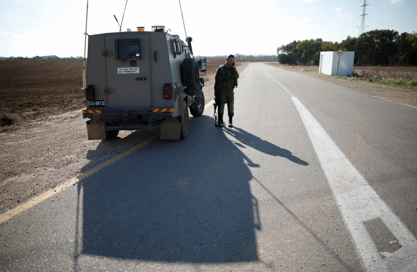 An Israeli soldier stands next to an armoured vehicle in kibbutz Nahal Oz, near the Gaza Strip border, Israel November 12, 2018 (photo credit: AMIR COHEN/REUTERS)
