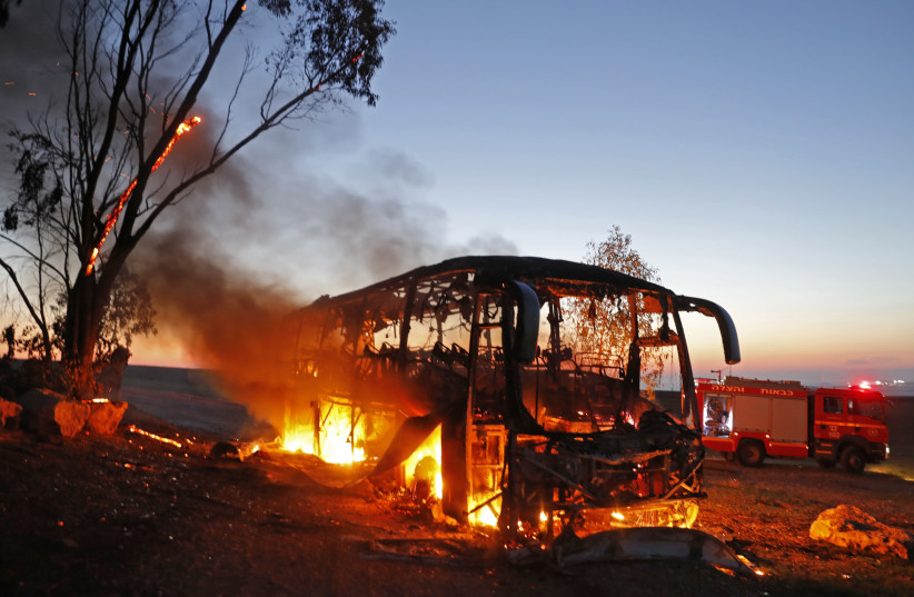 A picture taken on November 12, 2018 shows a bus set ablaze after it was hit by a rocket fired from the Gaza Strip (photo credit: MENAHEM KAHANA / AFP)