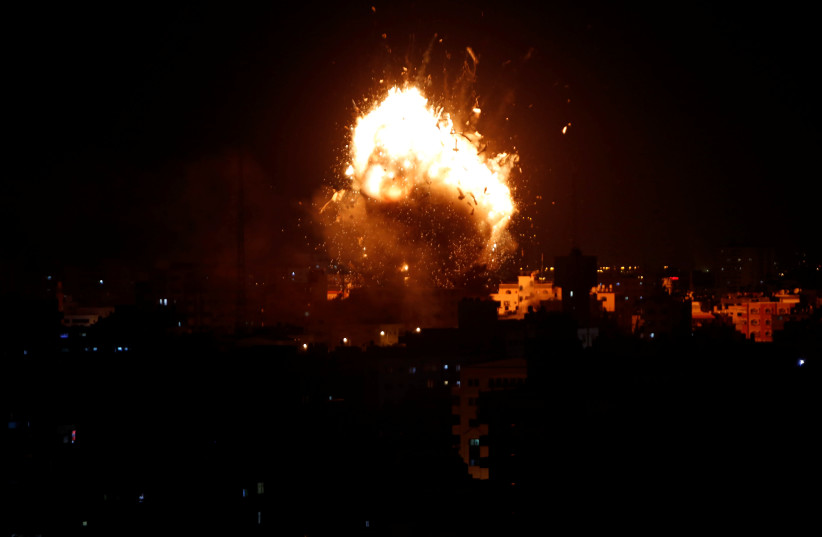 An explosion is seen during an Israeli air strike on Hamas's television station, in Gaza City November 12, 2018 (photo credit: REUTERS/AHMED ZAKOT)