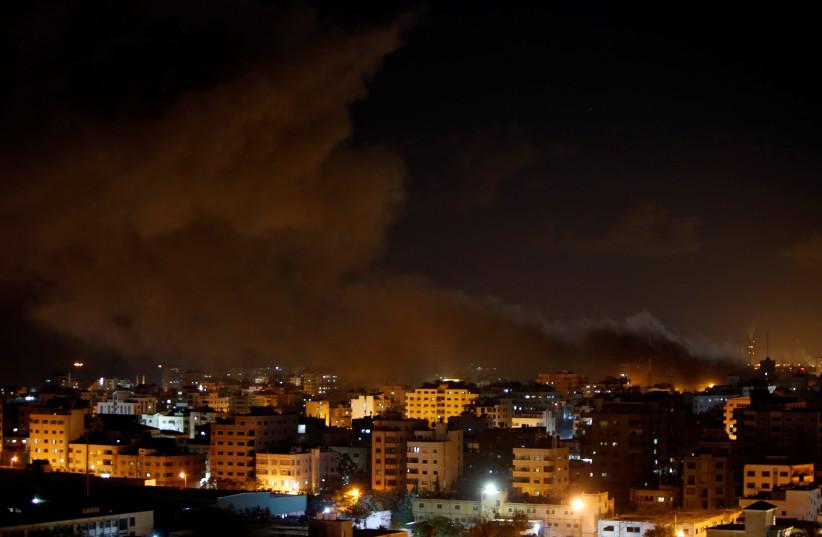 Smoke rises following an Israeli air strike on Hamas's television station, in Gaza City, November 12, 2018 (photo credit: AHMED ZAKOT / REUTERS)