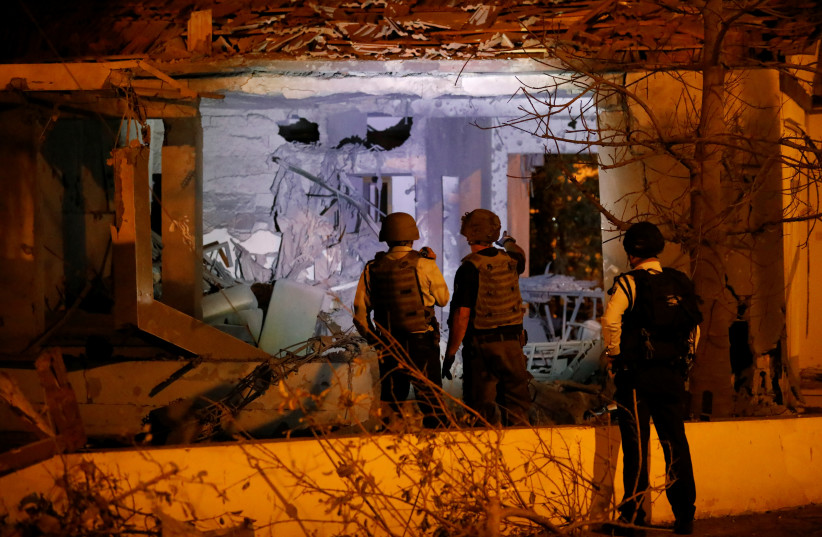 Security personnel check a damaged house in the Israeli city of Ashkelon, following a rocket attack from Gaza November 12, 2018.  (photo credit: REUTERS/AMIR COHEN)