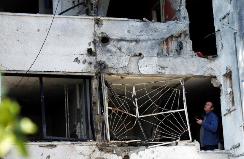 A man stands inside a building damaged by a rocket fired from the Gaza Strip overnight, in the Israeli city of Ashkelon November 13, 2018 (photo credit: RONEN ZVULUN / REUTERS)