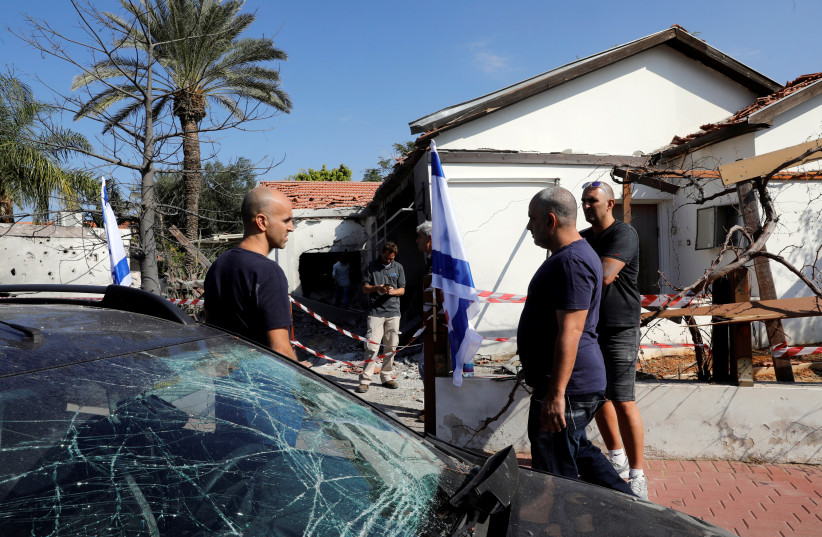 People stand next to a car and house damaged by a rocket fired from the Gaza Strip, in the Israeli city of Ashkelon November 13, 2018 (photo credit: RONEN ZVULUN / REUTERS)