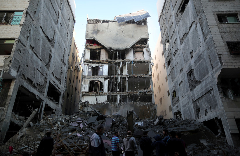 Palestinians gather near the remains of a building that was completely destroyed by an Israeli air strike, in Gaza City November 13, 2018.  (photo credit: REUTERS/SUHAIB SALEM)
