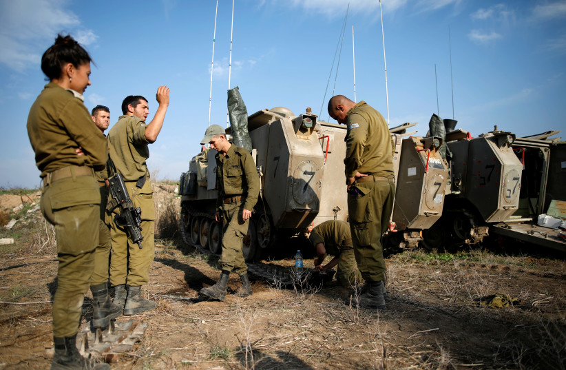 Israeli soldiers stand next to armoured personnel carriers (APC) in a field in southern Israel, near the border with Gaza, November 13, 2018 (photo credit: AMIR COHEN/REUTERS)