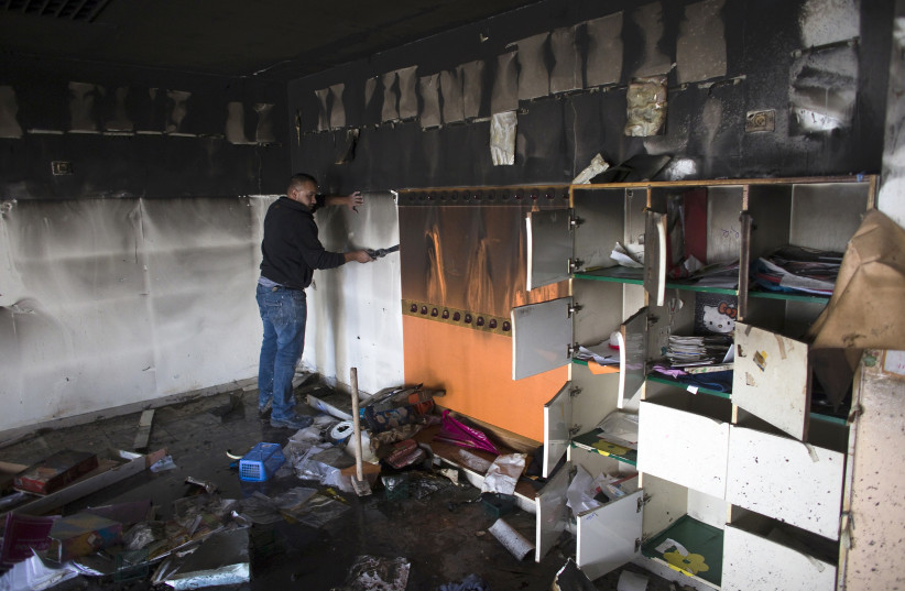 A worker cleans up in a torched classroom in an Arab-Jewish school in Jerusalem November 30, 2014 (photo credit: RONEN ZVULUN/REUTERS)