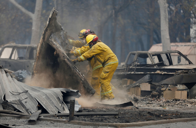 Cal Fire firefighters comb through a house destroyed by the Camp Fire in Paradise (photo credit: REUTERS/TERRAY SYLVESTER)