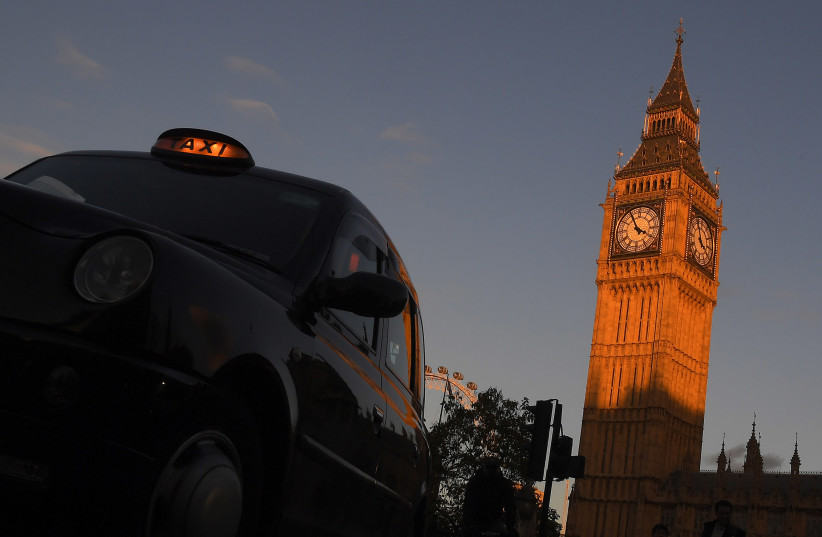 A London black cab taxi drives past Big Ben and the Houses of Parliament in late afternoon sunlight in London, Britain, November 10, 2016.  (photo credit: REUTERS/TOBY MELVILLE)