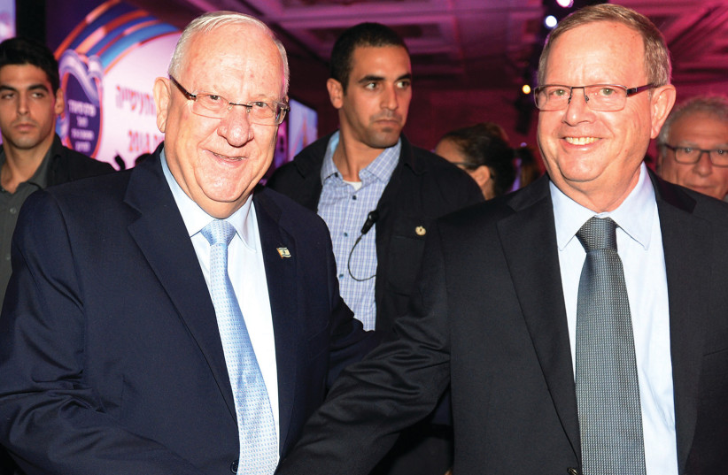 President Reuven Rivlin congratulates Ben and Jerry's Israel CEO Avi Zinger  (photo credit: MORAG BITAN)