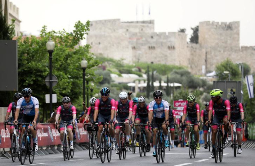 """Sylvan Adams (C, blue), honorary president of Giro d'Italia's """"Big Start"""" Israel, rides before the begining of the stage at the 101st Giro d'Italia cycling race in Jerusalem, May 4, 2018 (photo credit: AMMAR AWAD / REUTERS)"""