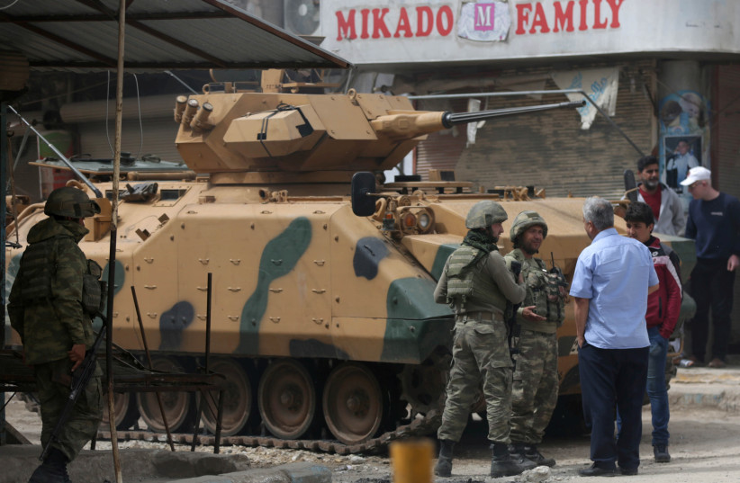 People speak with Turkish soldiers in the center of Afrin (photo credit: REUTERS)