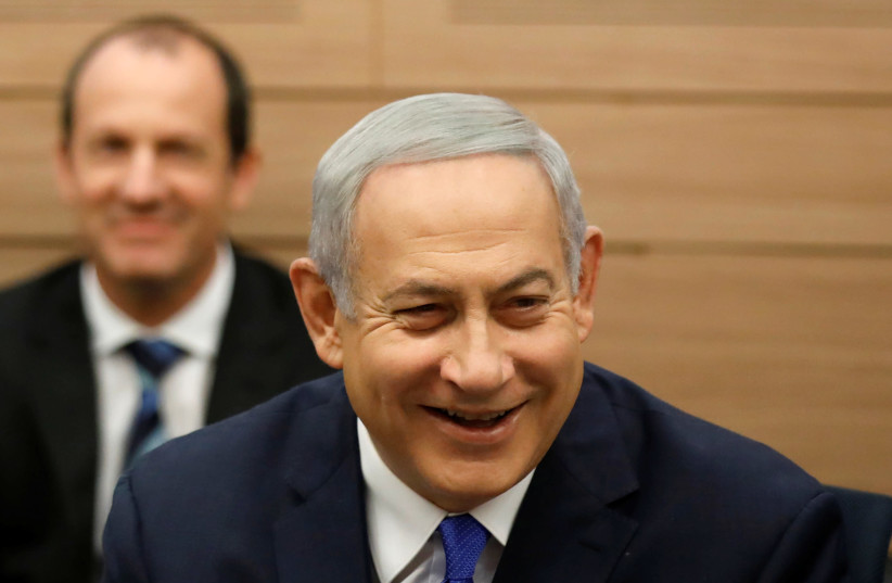 Israeli Prime Minister Benjamin Netanyahu smiles as he attends the Foreign Affairs and Defense Committee at the Knesset, Israel's Parliament, in Jerusalem November 19, 2018 (photo credit: AMIR COHEN/REUTERS)