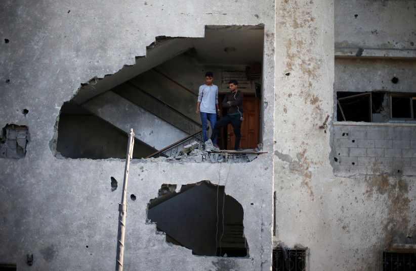 Palestinians look out of their house that was damaged in an Israeli air strike, in Gaza City November 13, 2018 (photo credit: REUTERS/SUHAIB SALEM)