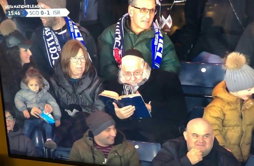 Rabbi studying during ISR-SCO game goes viral (photo credit: EYTAN HALON)