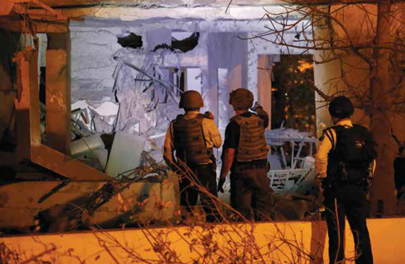 SECURITY PERSONNEL check a damaged house in Ashkelon following a rocket attack on November 12. (photo credit: REUTERS)