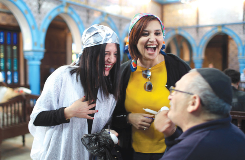 Two Tunisian Muslim women chat with a Jewish man at the El Ghriba Synagoguge (photo credit: AHMED JADALLAH / REUTERS)
