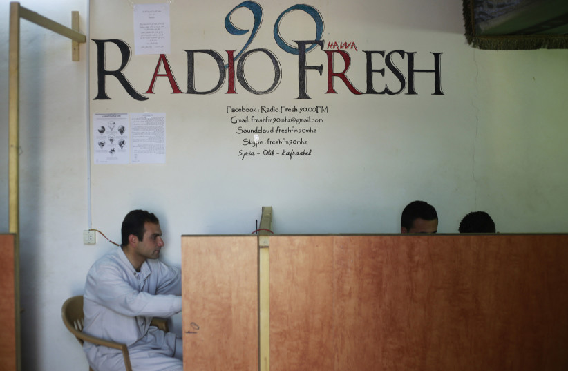 Activists sit at the premises of the Radio Fresh station in Kafranbel town in the Idlib governorate (photo credit: REUTERS/HAMID KHATIB)
