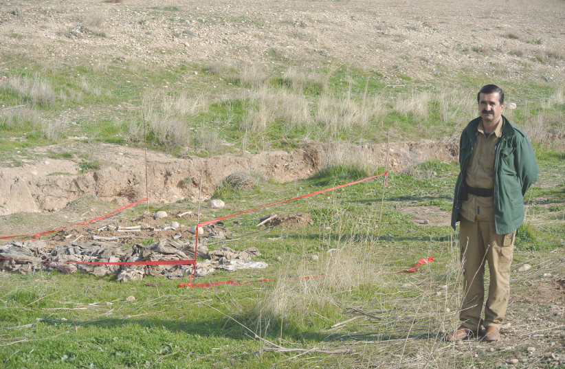 A Yazidi man stands next to a mass grave discovered in November 2015 after Kurdish forces liberated Sinjar from Islamic State (photo credit: SETH J. FRANTZMAN)