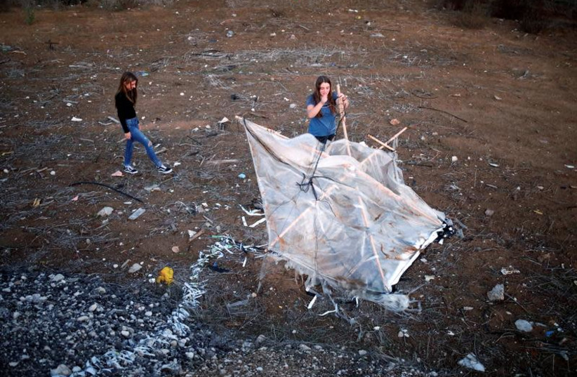 Israeli teens, Meshy Elmkies (R), 16, and Lee Cohen, 17, co-managers of Instagram account, Otef.Gaza, show Reuters journalists an incendiary kite launched from the Gaza Strip, during an interview in Kibbutz Kerem Shalom which borders the Gaza Strip, in southern Israel November 11, 2018 (photo credit: AMIR COHEN/REUTERS)