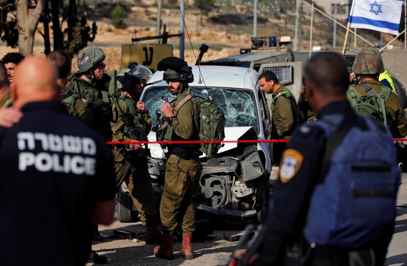 Israeli policemen inspect the scene of a car-ramming attack near Hebron, November 26, 2018 (photo credit: AMMAR AWAD/REUTERS)