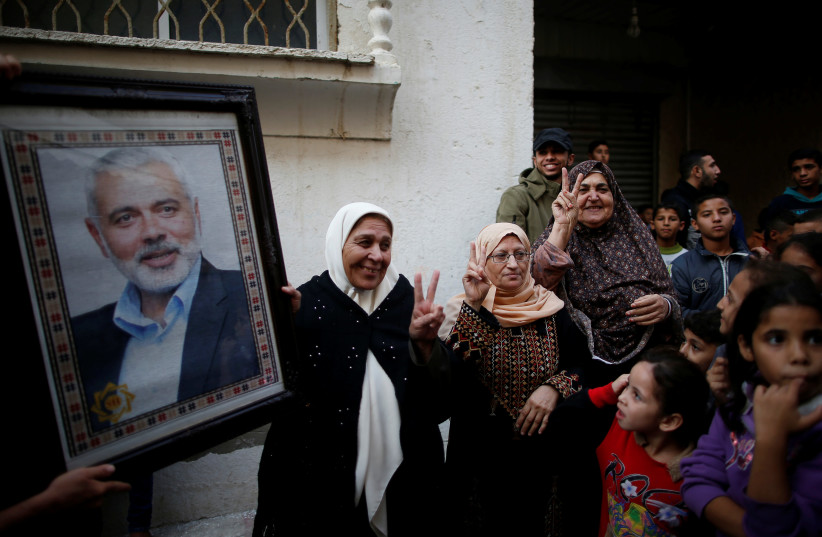 Palestinians celebrate the resignation of Israel's Defence Minister Avigdor Lieberman as a woman holds a picture of Hamas Chief Ismail Haniyeh, in Gaza City November 14, 2018 (photo credit: SUHAIB SALEM/REUTERS)