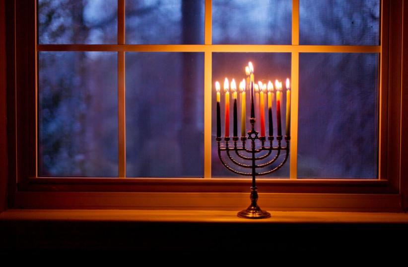 Menorah in the window on the eighth night (photo credit: AMANDA FIELD)