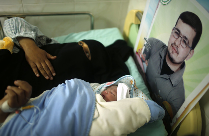 Hana, the wife of Palestinian prisoner Tamer al-Za'anin (pictured in poster), lies on a bed next to her baby boy al-Hassan, who was conceived with al-Za'anin's sperm smuggled out of an Israeli prison, at a hospital in Gaza City January 10, 2014 (photo credit: REUTERS/SUHAIB SALEM)