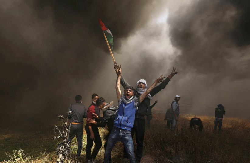 Palestinian demonstrators shout during clashes with Israeli troops at a protest demanding the right to return to their homeland, at the Israel-Gaza border east of Gaza City, April 6, 2018 (photo credit: REUTERS/MOHAMMED SALEM)