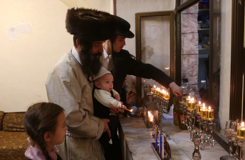 Lighting Hanukkah candles in Jerusalem's Mea She'arim neighborhood (photo credit: MARC ISRAEL SELLEM/THE JERUSALEM POST)