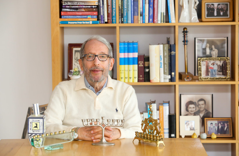 Rabbi Dov Peretz Elkins shows off several of his hanukkiot in his Jerusalem apartment; behind him are some of the 51 books he has published (photo credit: MARC ISRAEL SELLEM/THE JERUSALEM POST)
