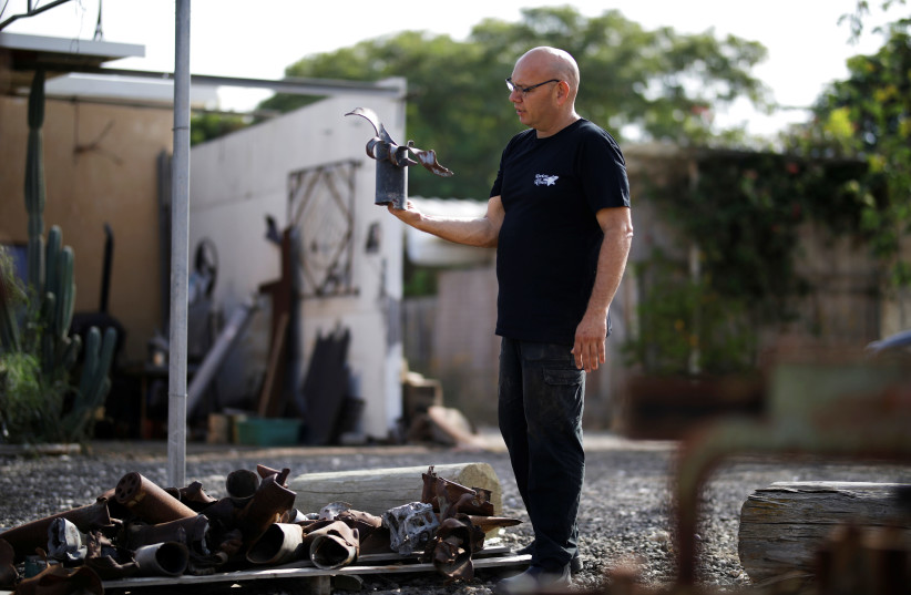 Israeli metal sculptor Yaron Bob looks at remains of rockets and mortar shells fired into Israel by Palestinian militants from Gaza, outside his studio in Yated, southern Israel  (photo credit: AMIR COHEN/REUTERS)