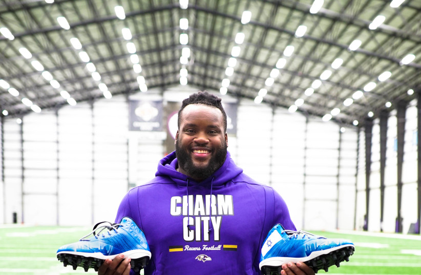 Baltimore Ravens' Michael Pierce holding his Israeli-themed cleats (photo credit: ISRAEL COLLECTIVE)
