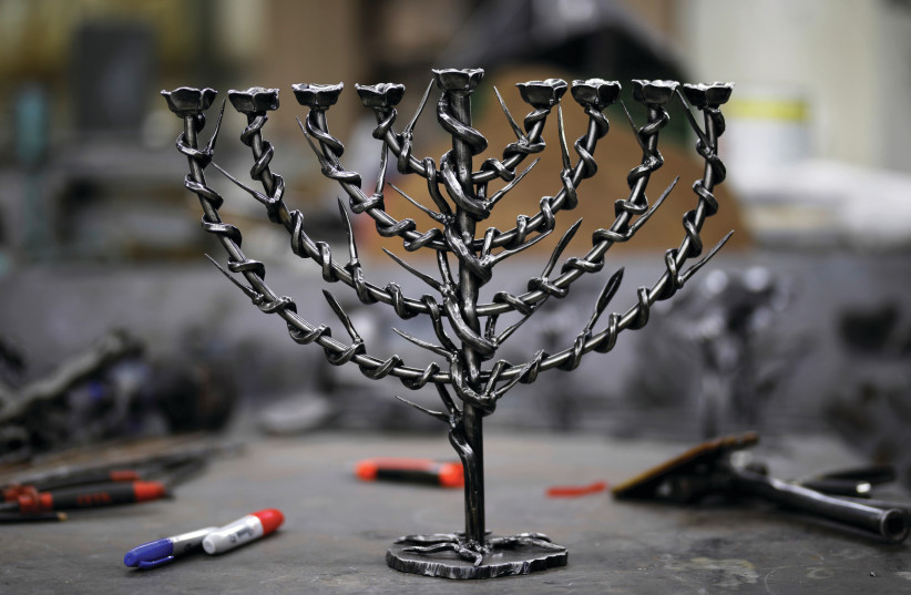 All Rabbinic commentaries agree that the light of Hanukkah candles may not be used for our own benefit - we are not even permitted to use the light from the flames to read in a dimly lit room (photo credit: REUTERS)