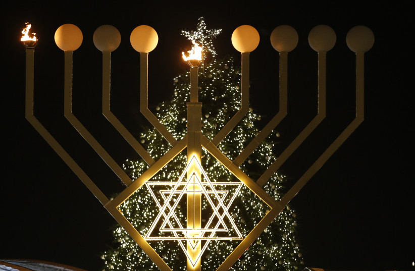 A giant menorah stands in front of a Christmas tree at the Brandenburg gate to celebrate Hanukkah in Berlin December 16, 2014 (photo credit: REUTERS/FABRIZIO BENSCH)
