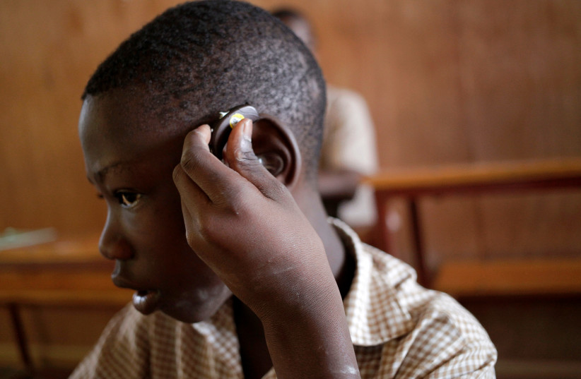 A deaf pupil puts a hearing aid on his ear at the Mission de L'Espoir school in Leveque, Haiti, April 11, 2016. (photo credit: REUTERS/ANDRES MARTINEZ CASARES)