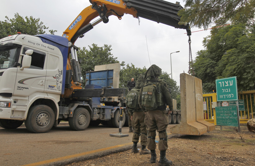 a crane laying a concrete T-wall block at a security checkpoint along a road near the northern Israeli town of Metula near the border with Lebanon, December 4, 2018 (photo credit: JALAA MAREY/AFP)