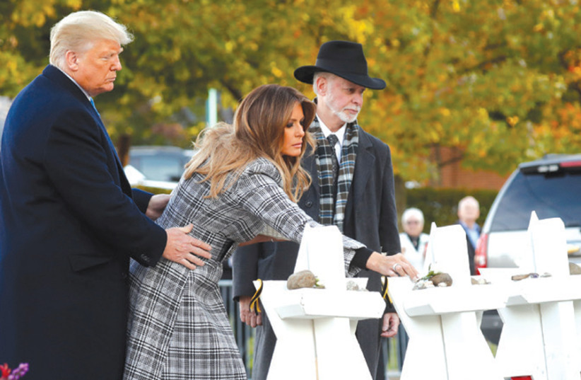 US President Donald Trump and First Lady Melania Trump place stones on a memorial to the 11 shooting victims as they stand with Rabbi Jeffrey Myers outside the Tree of Life Synagogue in Pittsburgh, on October 30 (photo credit: KEVIN LAMARQUE/REUTERS)