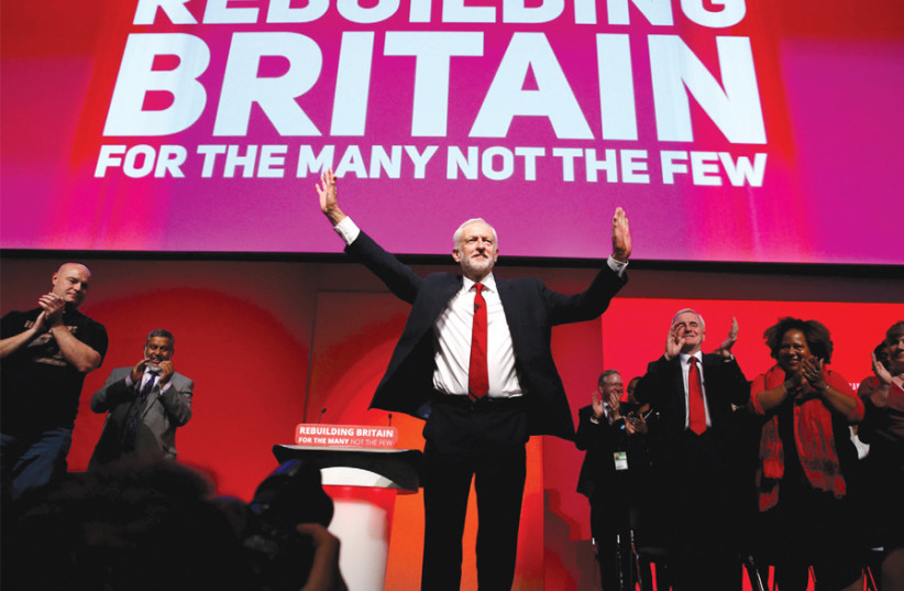 Jeremy Corbyn acknowledges an audience's applause (photo credit: PHIL NOBLE/REUTERS)