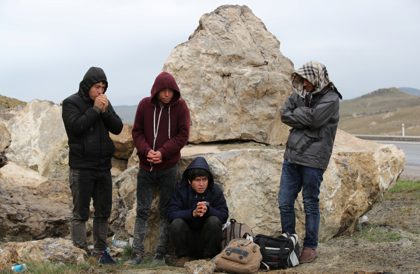 A group of Afghan migrants rest, during a break from their walk, on a main road, after crossing the Turkey-Iran border near Dogubayazit, Agri province, eastern Turkey, April 11, 2018. Picture taken April 11, 2018 (photo credit: REUTERS/UMIT BEKTAS)