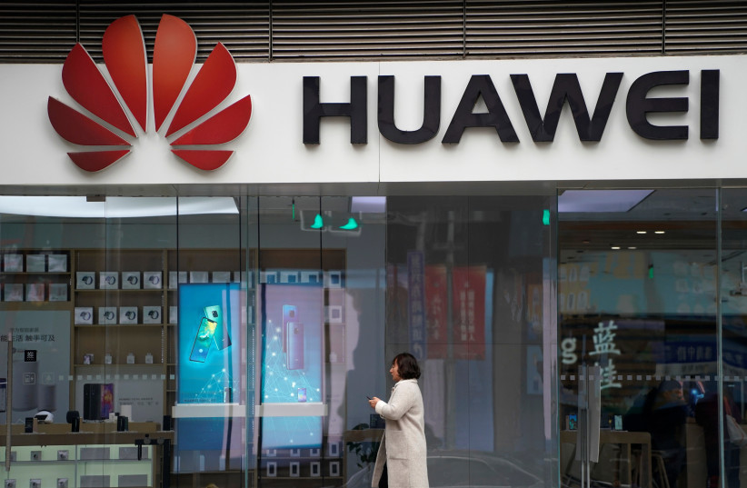 A woman walks by a Huawei logo at a shopping mall in Shanghai, China December 6, 2018 (photo credit: ALY SONG/REUTERS)