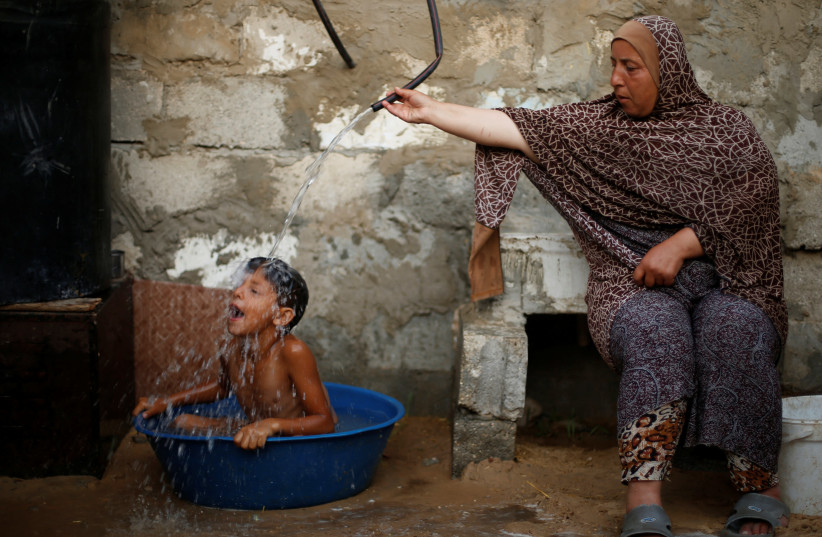 A Palestinian woman bathes her son with water from a tank, filled by a charity, inside their dwelling in Khan Younis, in the southern Gaza Strip (photo credit: MOHAMMED SALEM/REUTERS)