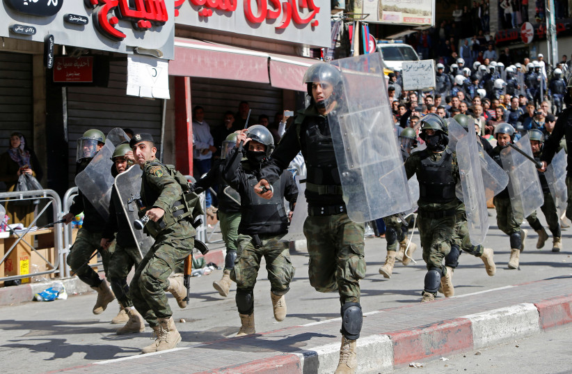 Members of the Palestinian security forces clash with demonstrators during a protest organised by Hizb-ut Tahrir against what organisers say are political arrests by the Palestinian Authority in the West Bank city of Hebron February 25, 2017. (photo credit: REUTERS/MUSSA QAWASMA)