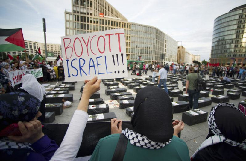 """A woman holds a sign which reads """"Boycott Israel"""" in front of symbolic coffins while attending a demonstration supporting Palestine, in Berlin August 1, 2014. Israel launched its Gaza offensive on July 8 in response to a surge of rocket attacks by Gaza's dominant Hamas Islamists. Hamas said that Pal (photo credit: REUTERS/STEFFI LOOS)"""