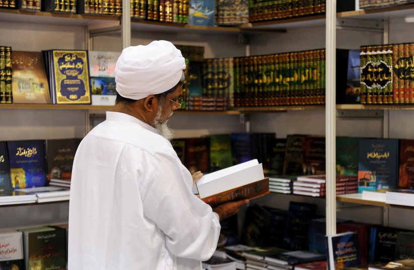 A handout picture released by the Qatari ministry of culture shows a man browsing through a book at the Doha International Book Fair in the Qatari capital on November 25, 2010 (photo credit: AFP PHOTO/HO)
