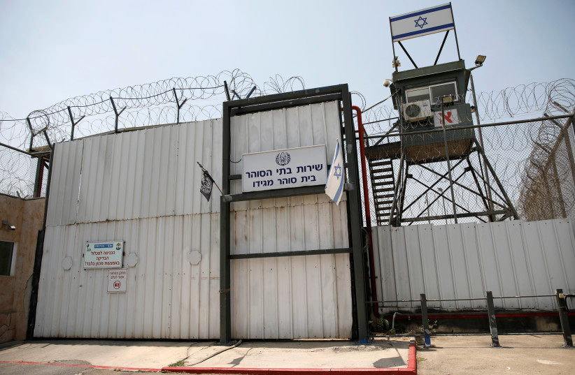 An Israeli flag is seen next to the gate of the Megiddo Prison in northern Israel July 24, 2018. Picture taken July 24, 2018.  (photo credit: REUTERS/AMIR COHEN)