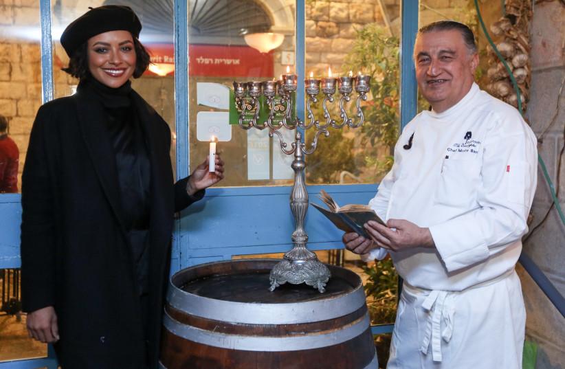 Actress Kat Graham and Eucalpytus chef Moshe Basson light candles for Hanukkah at the restaurant in Jerusalem Thursday night (photo credit: MARC ISRAEL SELLEM/THE JERUSALEM POST)